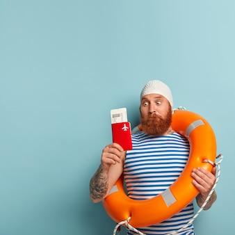 L'uomo barbuto stupefatto fissa scioccato sul passaporto e sui biglietti aerei, si prepara per il viaggio di volo in località turistica durante le vacanze estive