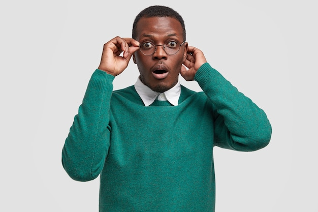 Stupefied black man with amazed facial expression, keeps hand on rim of spectacles, dressed in casual green sweater