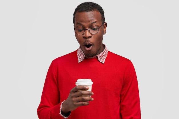 愚かな黒人の若い男はコーヒーブレイクをし、対話者から素晴らしいニュースを聞き、使い捨てカップを持ち、息を切らし、赤いセーターを着ています