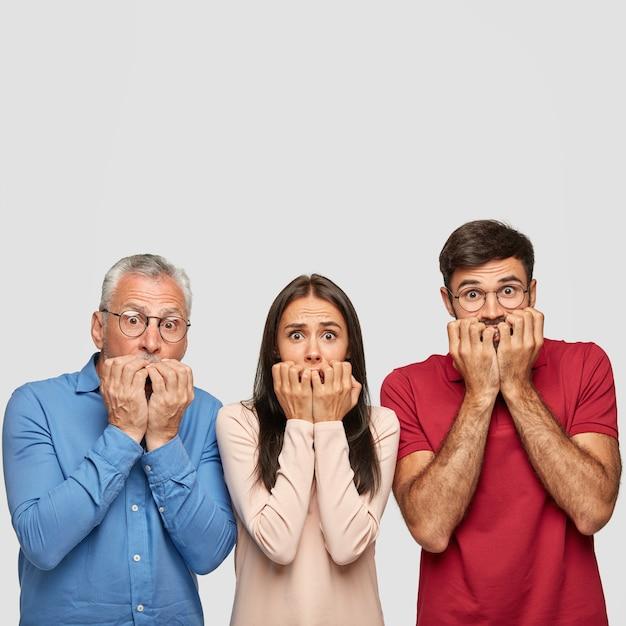 Stupito fratello, sorella e il loro anziano padre in posa contro il muro bianco