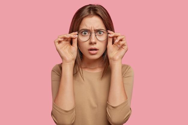 Ошеломленная кавказская женщина смотрит сквозь очки, не может поверить своим глазам, эмоциональна, находится в ступоре от внезапных новостей, у нее прямые волосы, она одета в повседневную одежду, изолирована за розовой стеной.