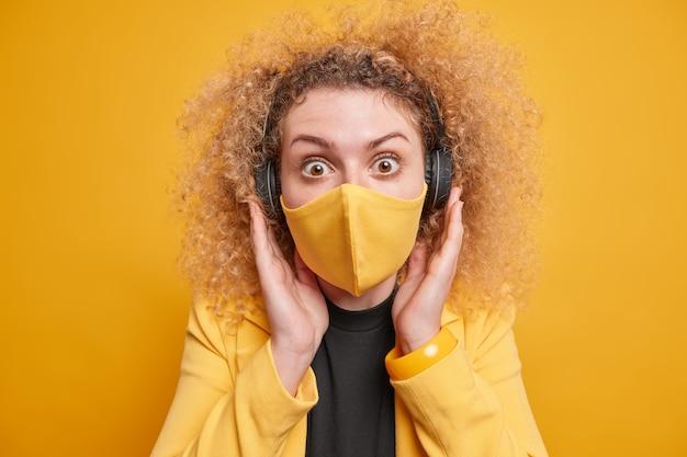 Stupefatta donna dai capelli ricci tiene le mani sulle cuffie fissa indossa una maschera usa e getta protegge dal coronavirus evita l'infezione indossa abiti formali pose contro il muro giallo.