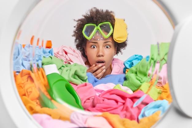 어리둥절한 곱슬머리 여성은 스노클링 마스크를 착용하고 세탁기 내부에서 세탁할 준비가 된 여러 가지 빛깔의 세탁물 더미에서 곱슬머리 포즈에 양말을 끼고 세제를 확인합니다
