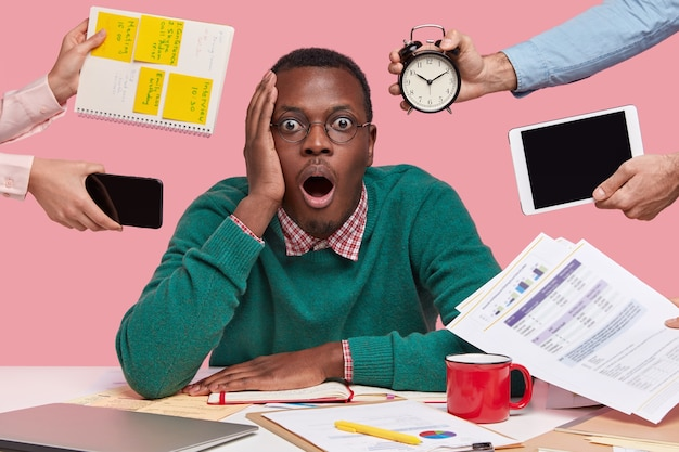 Stupefied dark skinned guy opens mouth from fear, expresses great surprisement and wonder, being overload with much paper work