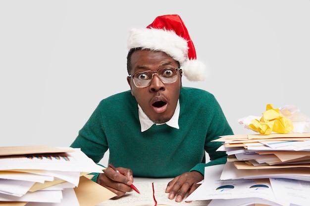 Ошеломленный темнокожий мужчина с удивлением открывает рот, носит очки и красную праздничную шляпу, удивленный множеством заданий.