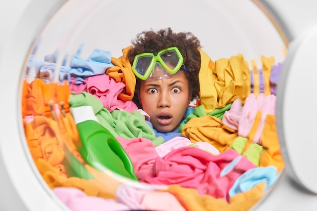 Stupefied embarrassed housewife stares with shock sticks head through stack of laundry busy doing domestic chores poses in washing machine overloaded by housework