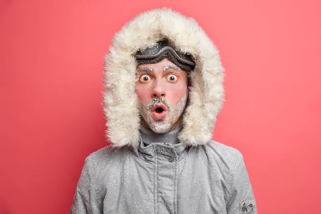 어리둥절한 감정적 인 남성 관광객은 산에서 겨울 휴가를 보내고 야외에서 활동적인 스포츠를 즐기고 흰 서리로 덮인 대단한 경이에서 입을 벌리고 재킷과 스노우 보드 고글을 착용합니다.