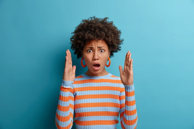 Stupefatta donna emotiva impressionata dalle grandi dimensioni, alza i palmi e mostra qualcosa di enorme, apre la bocca e spiega, forma oggetti invisibili, allarga le braccia, indossa un maglione a righe, isolato su blu
