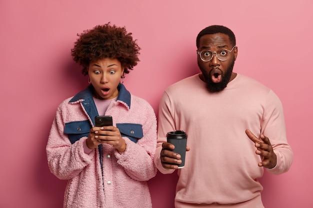 愚かな感情的な女性はスマートフォンのディスプレイを見つめ、奇妙なテキストメッセージを受け取り、驚いたひげを生やした男は持ち帰り用のコーヒーを飲みます