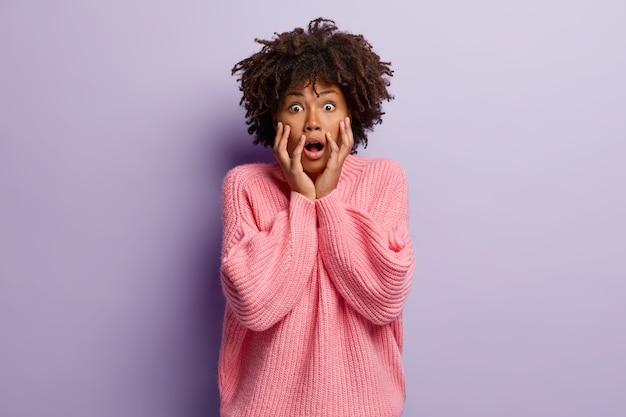 愚かな感情的な女性は、omgの外観で見つめ、頬に手を保ち、顎を落とし、衝撃的なニュースを信じることができず、ジャンパーを着て、紫色の壁にモデルを置きます。人とショックの概念