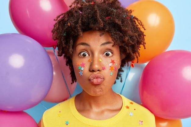 Stupefatta giovane donna emotiva in posa circondata da palloncini colorati compleanno