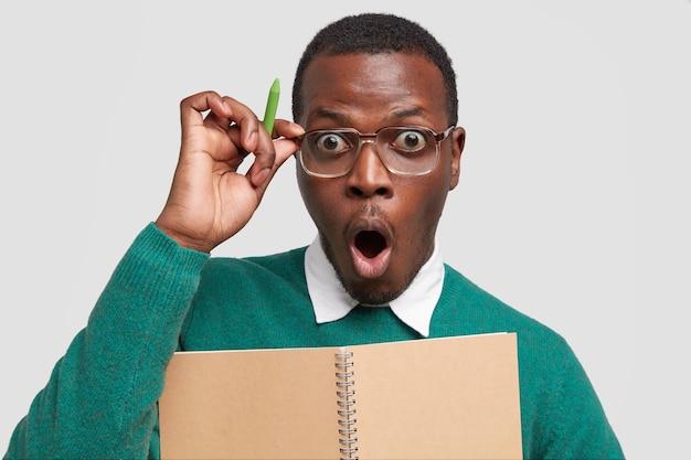 Ошеломленный эмоциональный темнокожий мужчина широко открывает рот, держит ручку, держит руку на оправе очков и слышит шокирующие новости