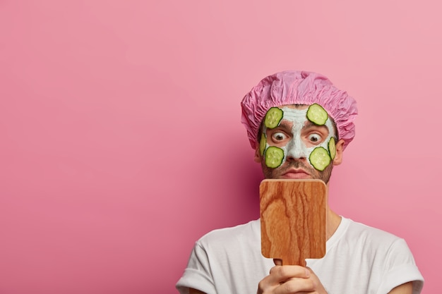 Stupefatto modello maschio europeo guarda allo specchio, applica una maschera all'argilla con cetrioli, ha trattamenti di bellezza nel salone della spa, vestito con maglietta bianca e cuffia da bagno