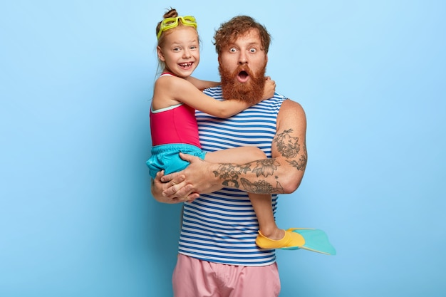 Stupefied ginger father and daughter posing in pool outfits