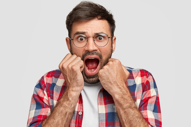 愚かなハンサムな男は怖い表情で見え、顎を落とし、手を口の近くに保ち、恐れをもって叫び、白い壁に隔離された素晴らしい何かに気づきます。否定的な感情