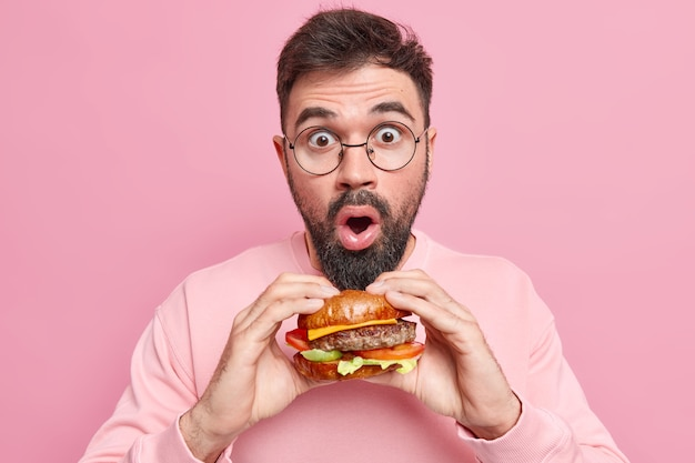 Stupefied handsome man poses with delicious appetizing fast food holds tasty hamburger wears round spectacles casual jumper doesnt keep to diet likes cheat meal dressed casually