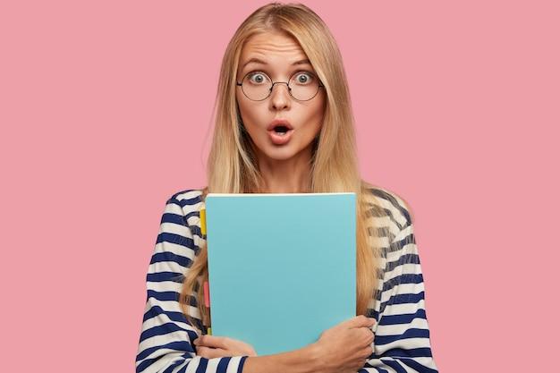 目がバグ、息を切らして、自分の近くに青いフォルダーを持っている愚かな明るい髪の白人女性