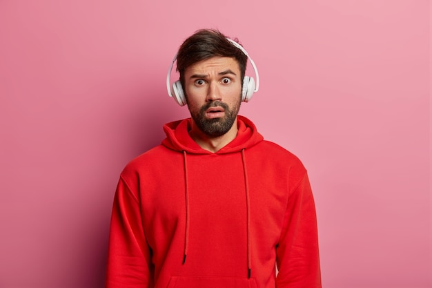 Stupefied male meloman stares surprisingly , listens audio via headphones, dressed in red sweatshirt, hears astonishing news, poses over rosy wall. people, reaction, emotions.