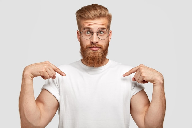 Stupefied red haired man has thick beard, points at copy space of t shirt, shows place for slogan or logo