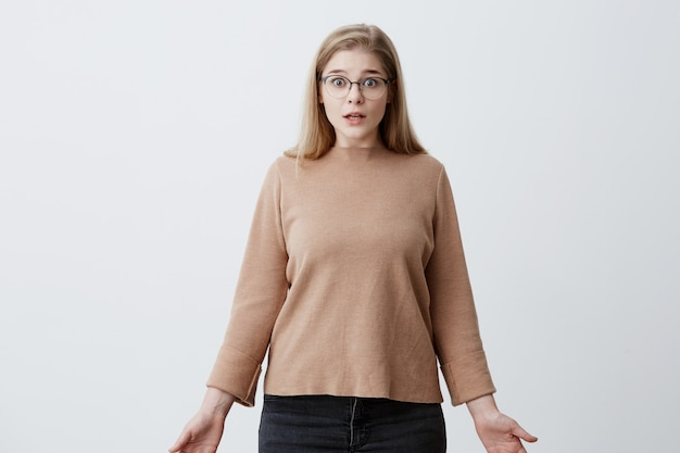 Stupefied shocked woman looks with shocked expression , with bugged eyes, astonished to hear shocking news. caucasian female in eyewear has puzzled look, isolated