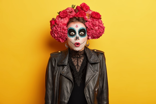 Stupefied terrified woman with ghost painted face, dressed in lace black dress, leather jacket, red flower made wreath stands over color background