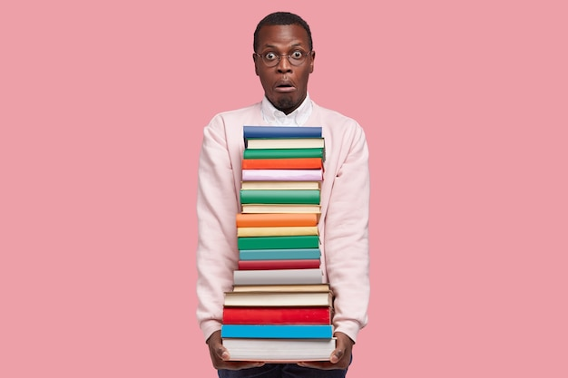 Stupefied young afro american man with big pile of books, dressed in casual sweater, has surprised facial expression