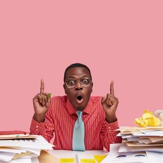 Stupefatto giovane manager nero ha gli occhi spalancati, vestito con camicia formale rosa e cravatta, punta verso l'alto con entrambi gli indici