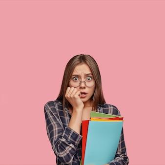 Ошеломленная молодая деловая женщина позирует на розовой стене в очках