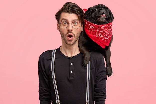 Il giovane maschio stupefatto porta il suo cane di razza nero sul collo, vestito con una camicia alla moda con bretelle, nota qualcosa di sorprendente, isolato su un muro rosa. buon concetto di relazioni.