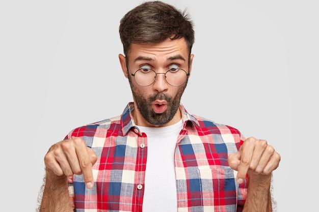 Ошеломленный молодой небритый мужчина в повседневной рубашке и очках, удивленно смотрит вниз, указывает в пол