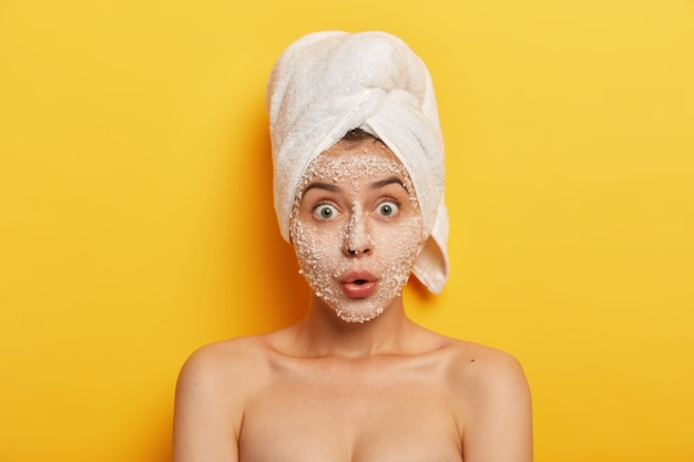 Stupefied young woman applies natural sea salt mask, reduces acnes and pimples, stares with widely opened eyes, healthy skin, cares about complexion, has spa therapy in bathroom. hygiene and wellness
