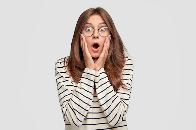 Ошеломленная молодая женщина в очках позирует у белой стены