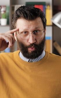멍청한. 사무실이나 아파트 방에서 안경을 쓴 수염난 남자는 카메라를 보고 관자놀이에서 손가락을 돌립니다. 클로즈업 보기