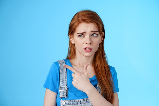 Stupified redhead hesitant girl show aversion, pointing looking left reluctant, full disbelief, stare with dismay uncertain about product, disliking strange weird guy standing blue background