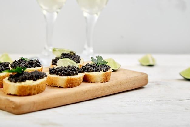 Черная икра осетровых рыб в деревянной миске, бутерброды и шампанское.