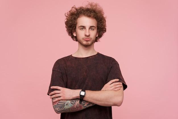 Foto di stusio di bel giovane maschio rosso barbuto riccio in abiti casual che piegano le mani sul petto e che guarda l'obbiettivo con viso calmo, isolato sopra il muro rosa