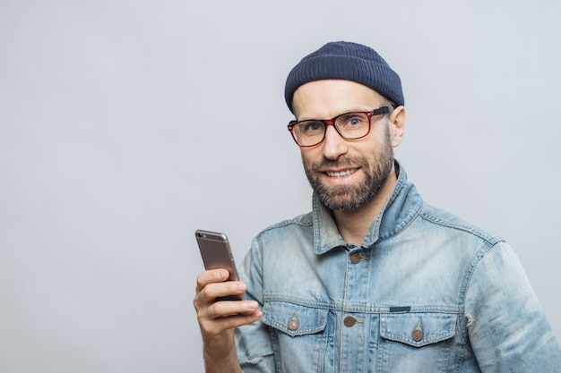 Stusio shot of happy bearded man with stubble holds modern smart phone in hands