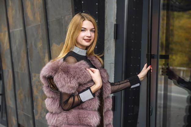スタイルとファッション。反射ドアの近くに立っている毛皮のコートのブロンドの女性