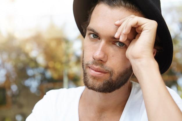 스타일과 패션. 검은 유행 모자를 쓰고 힙 스터 수염을 가진 젊은 백인 모델의 매우 상세한 샷