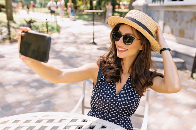 Style beautiful woman with short dark hair and charming smile is sitting in the summer cafeteria in sunlight. she is wearing summer hat and sunglasses and making selfie.