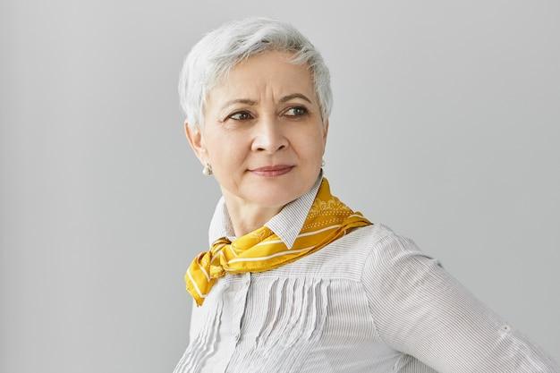 スタイル、美しさ、年齢のコンセプト。真珠のイヤリング、ブラウス、黄色いシルクのスカーフを首にかけ、自信を持って表情を見せているファッショナブルな白髪の成熟したヨーロッパの女性