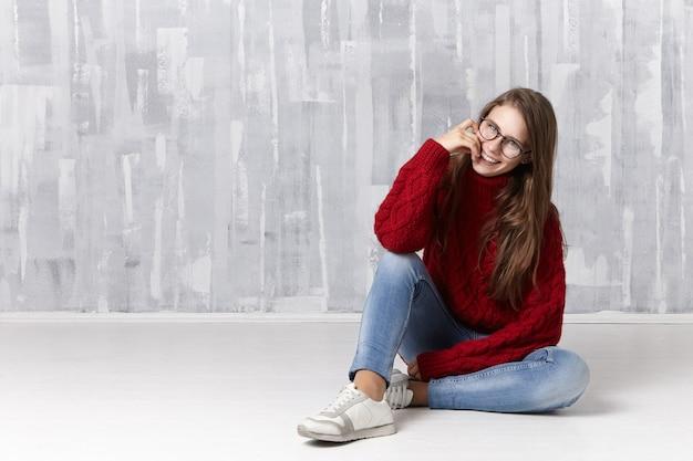 스타일, 뷰티, 패션, 의류 및 안경 개념. 느슨한 머리가 바닥에 앉아 장난스럽게 웃고, 그녀의 입술을 만지고, 안경, 스웨터, 청바지 및 운동화를 착용 한 트렌디 한 찾고 십대 소녀