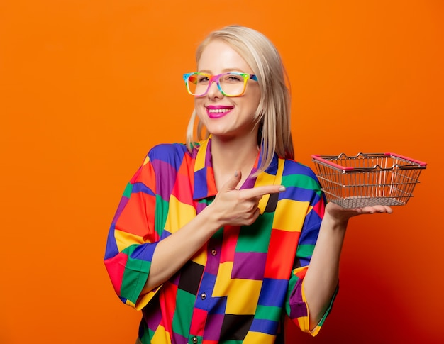 Style blonde in 90s clothes with shoping basket on orange