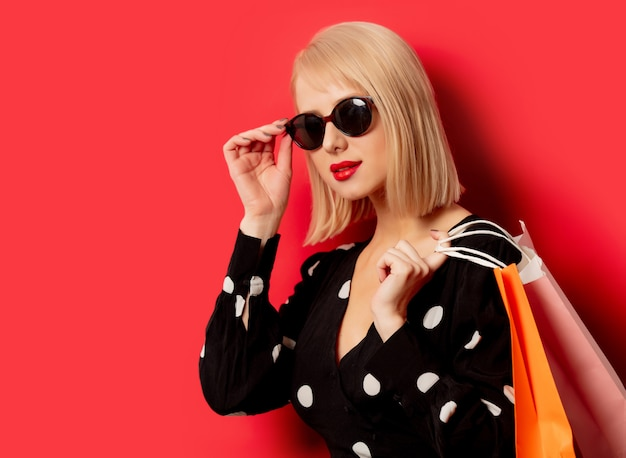 Style blonde girl in sunglasses with shopping bags on red wall