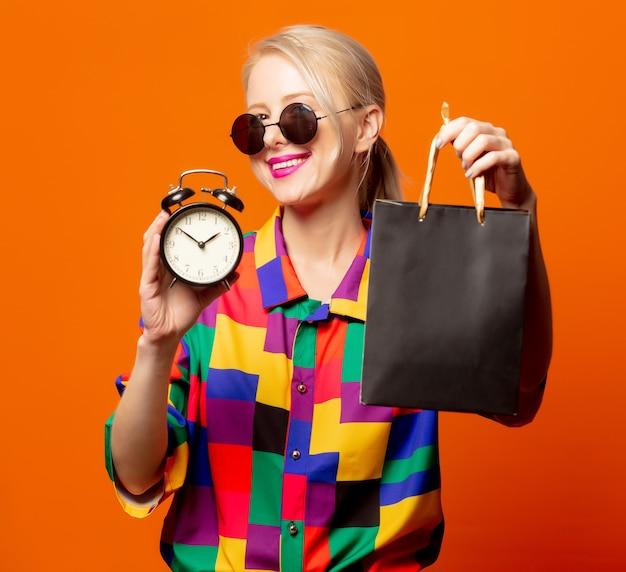 オレンジ色のショッピングバッグと90年代のシャツとメガネで金髪のスタイル