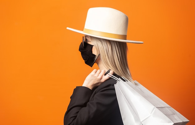 鮮やかなオレンジ色の背景にショッピングバッグと黒のブレザーと白い帽子で金髪のスタイル