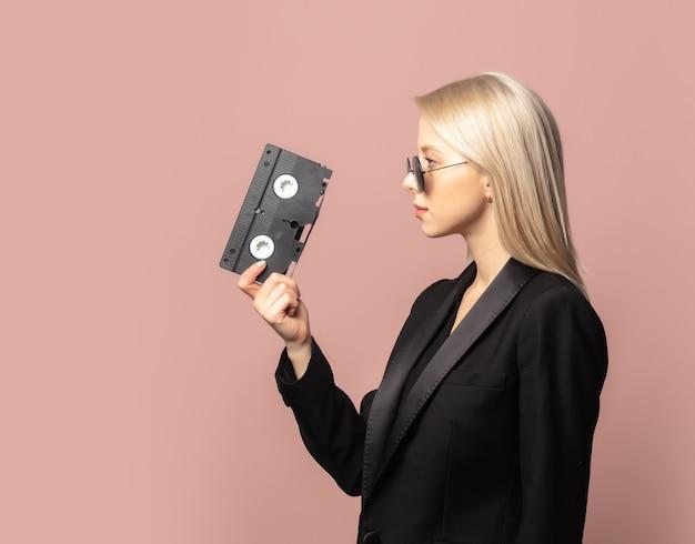 ピンクの背景にvhsテープで黒のブレザーで金髪のスタイル