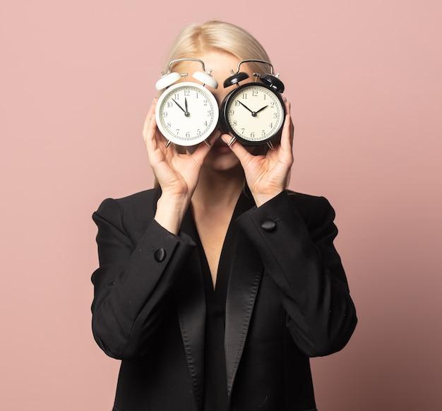 Блондинка в стиле пиджак и солнцезащитные очки с будильниками на розовом