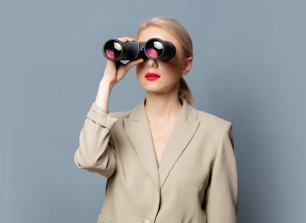 Стильная блондинка в куртке с биноклем на сером пространстве