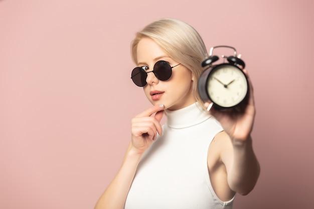 분홍색에 알람 시계가있는 상단과 선글라스의 스타일 금발